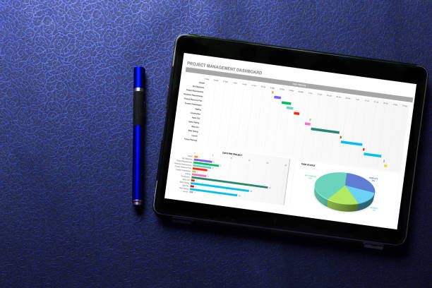 Excel project dashboard concept on tablet screen with blue pen on blue pattern textured background stock photo