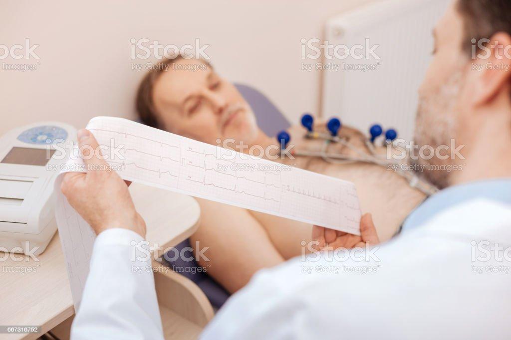 Excelente cardiologista treinada estudar cuidadosamente o cardiograma de pacientes - foto de acervo