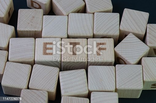 ETF, Exchange Traded Fund concept, cube wooden block with alphabet building the word ETF at the center on dark blackboard background.