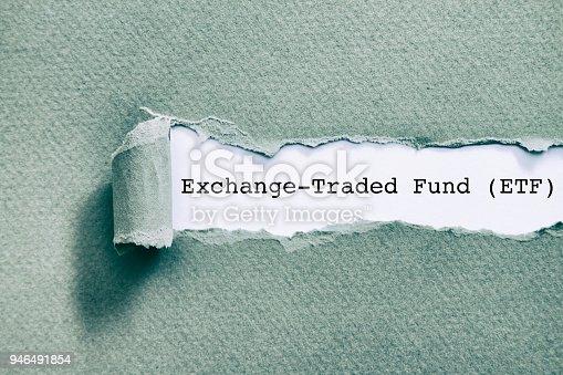 Exchange Traded Fund (ETF) written under torn paper.