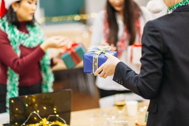 exchanging christmas gifts - office party stock pictures, royalty-free photos & images