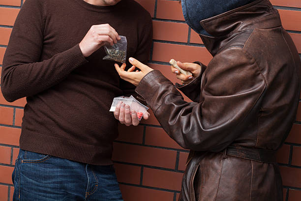 Exchanging drugs for money Students exchanging selected type of drugs for money drug dealer stock pictures, royalty-free photos & images