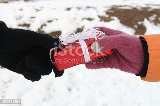 Male and female hand in winter gloves exchanging a gift against white snow background. Christmas concept