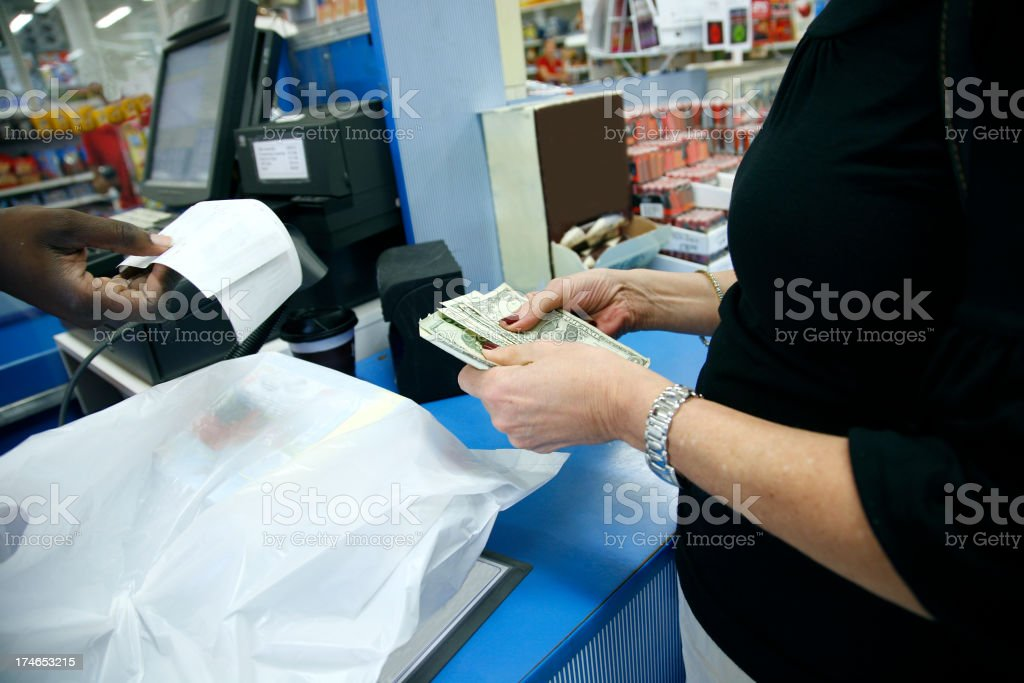 Exchanging money for receipt at grocery register stock photo