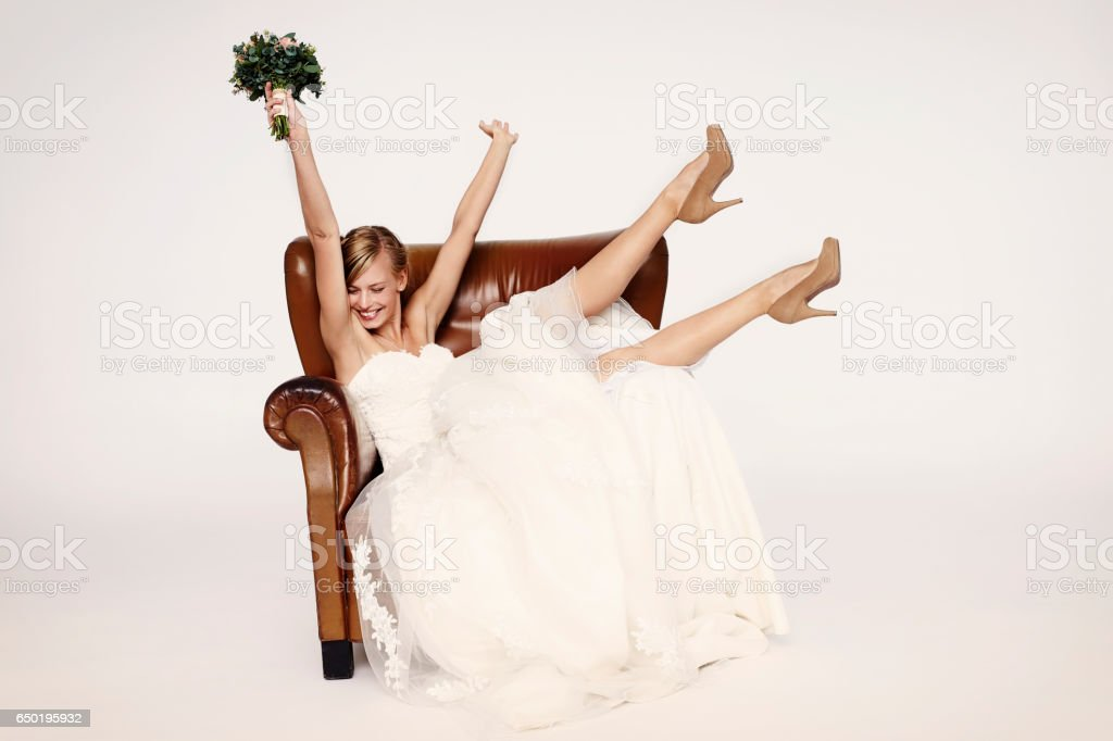Excitable bride in armchair stock photo