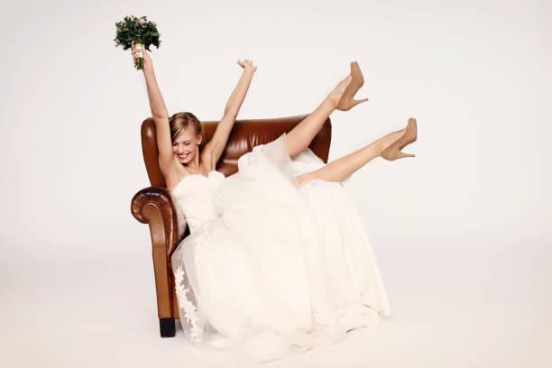 Excitable bride in armchair stock photo