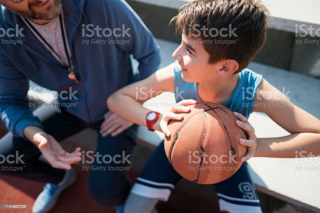 Unrecognizable coach explaining to a teenage boy how to hold a...