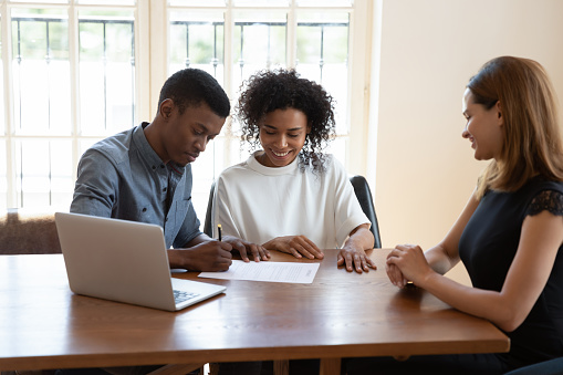 Excited African American husband and wife sit at desk meet with female agent close deal sign agreement, happy biracial couple put signature on contract document consult with realtor in office