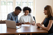 istock Excited african American couple close deal at agent office 1272592623