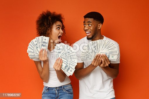 Excited african american couple holding bunch of money banknotes and looking at each other in amazement, orange studio background
