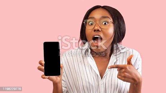 1159261513 istock photo Excited African American Girl Holding Phone Pointing Finger, Studio, Mockup 1198229776