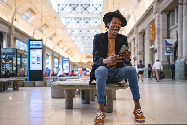 Excited African American man holding a mobile phone stock photo