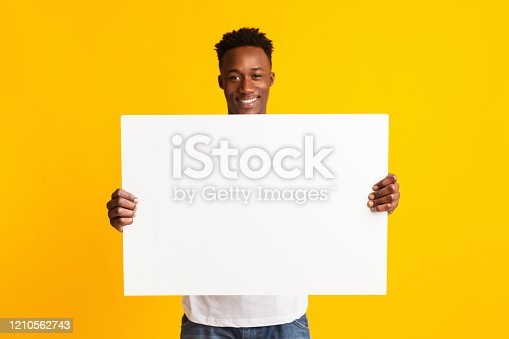 1159989540 istock photo Excited african american man holding blank poster 1210562743