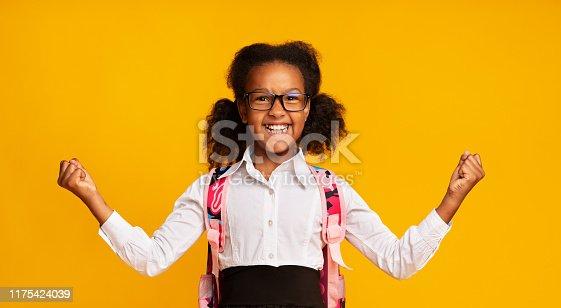 Excited African American Schoolgirl Gesturing Yes Rejoicing Success On Yellow Background In Studio. School Winner