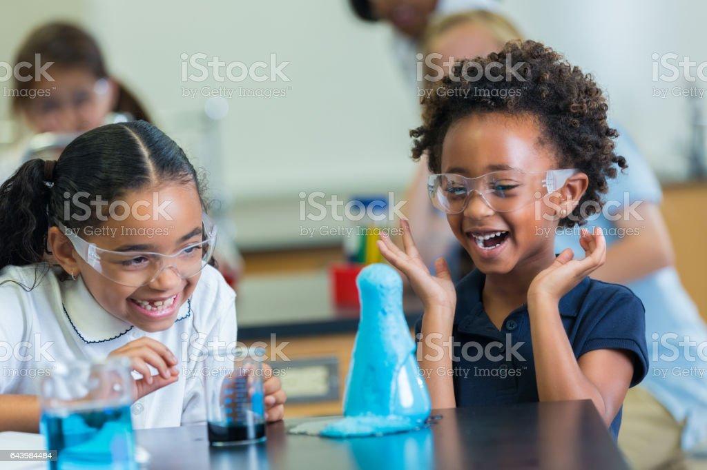 Excited African American schoolgirls enjoy science experiment stock photo