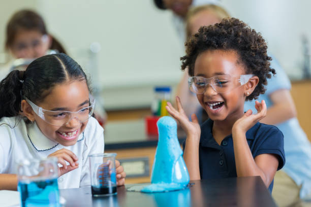 Excited African American schoolgirls enjoy science experiment stock photo