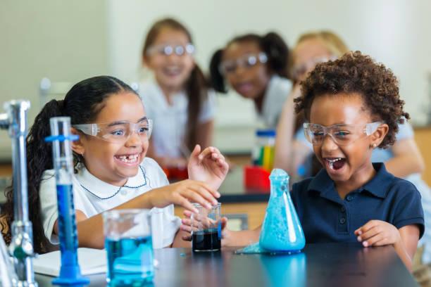 aufgeregte afroamerikanische schülerinnen teilnehmen im chemie-experiment - versuche nicht zu lachen stock-fotos und bilder
