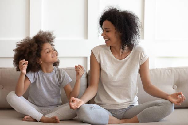 mujer afroamericana emocionada practicando yoga con hija pequeña. - hija fotografías e imágenes de stock