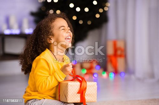 Excited african girl laughing with Christmas gift, empty space