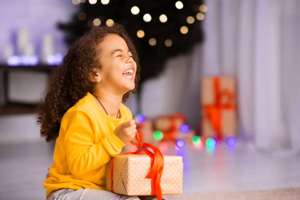 excited african girl laughing with christmas gift - regalo natale foto e immagini stock
