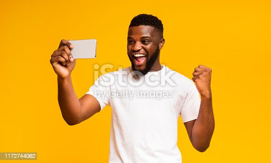 istock Excited African Guy Celebrating Success, Using Smartphone over Yellow Background 1172744062