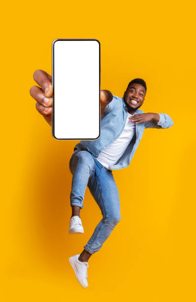 Excited african guy dancing with modern smartphone stock photo