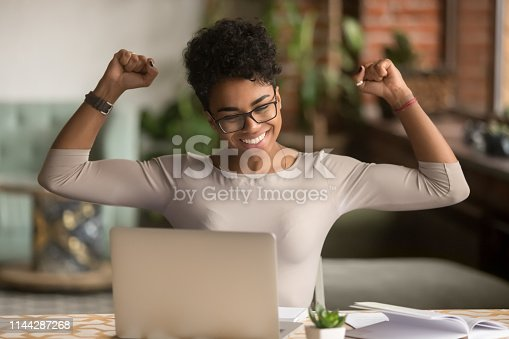 istock Excited african woman feeling winner rejoicing online win on laptop 1144287268