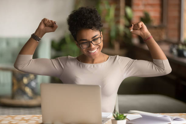 excited african woman feeling winner rejoicing online win on laptop - incentivo foto e immagini stock