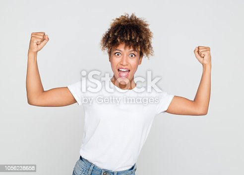657442382istockphoto Excited african woman flexing her biceps 1056238658