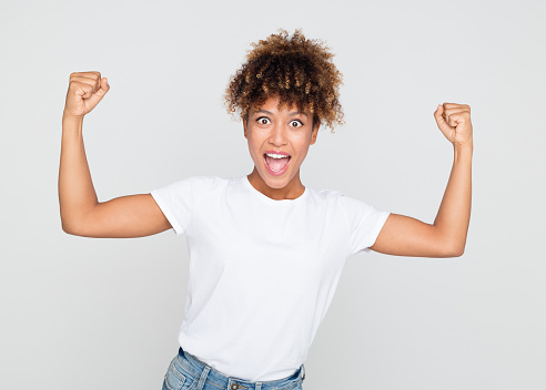 657442382 istock photo Excited african woman flexing her biceps 1056238658