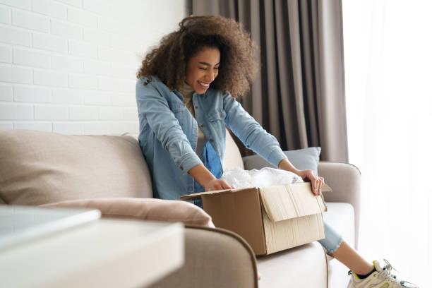 aufgeregt afrikanische junge frau käufer öffnen paketbox zu hause. glücklich zufrieden ethnische mädchen kunde erhalten online-shop-kauf per postversand, auspacken lieferung erhalten geschenk sitzen auf dem sofa. - bekommen stock-fotos und bilder