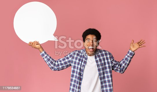 Excited african-american guy holding blank speech bubble, pink studio background
