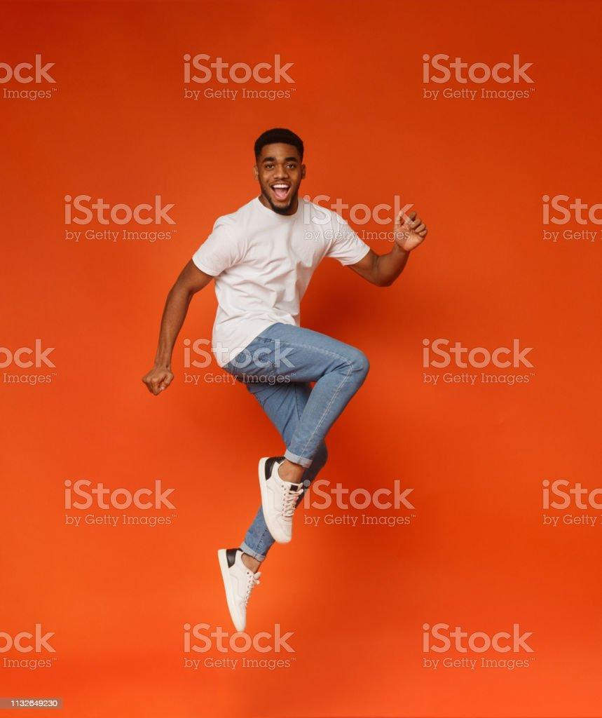 Turuncu arka planda atlama heyecanlı Afrikalı-Amerikan adam - Royalty-free 13 - 19 Yaş arası Stok görsel