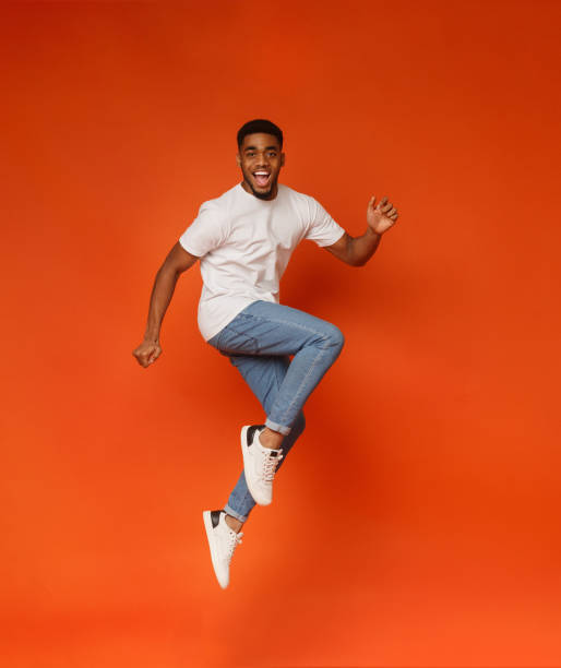 Excited african-american man jumping on orange background Funny portrait on young african-american man in humorous jump on orange background mid air stock pictures, royalty-free photos & images