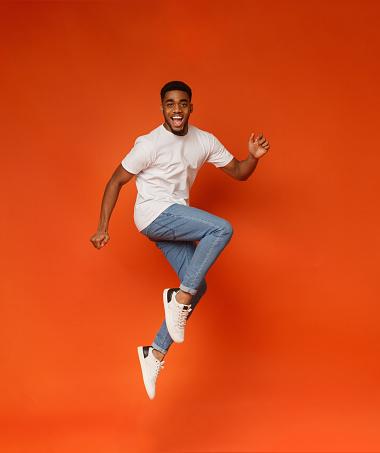 Turuncu Arka Planda Atlama Heyecanlı Afrikalıamerikan Adam Stok Fotoğraflar & 13 - 19 Yaş arası'nin Daha Fazla Resimleri