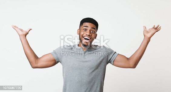 istock Excited african-american man raising his hands in happiness 1070087720