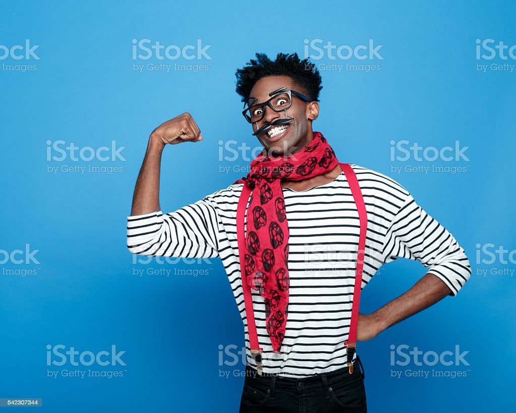 Excited afro american guy in a french outfit flexing bicep Portrait of excited afro american guy wearing striped long sleeved t-shirt, red suspenders and neckscarf, flexing his bicep and grining at the camera. Studio shot, blue background.  Adult Stock Photo