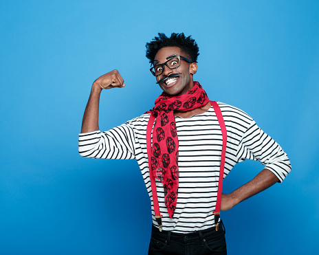 Excited Afro American Guy In A French Outfit Flexing Bicep Stock Photo - Download Image Now