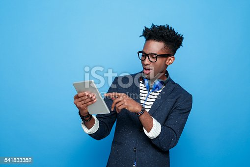 istock Excited afro american guy in fashionable outfit, holding digital tablet 541833352