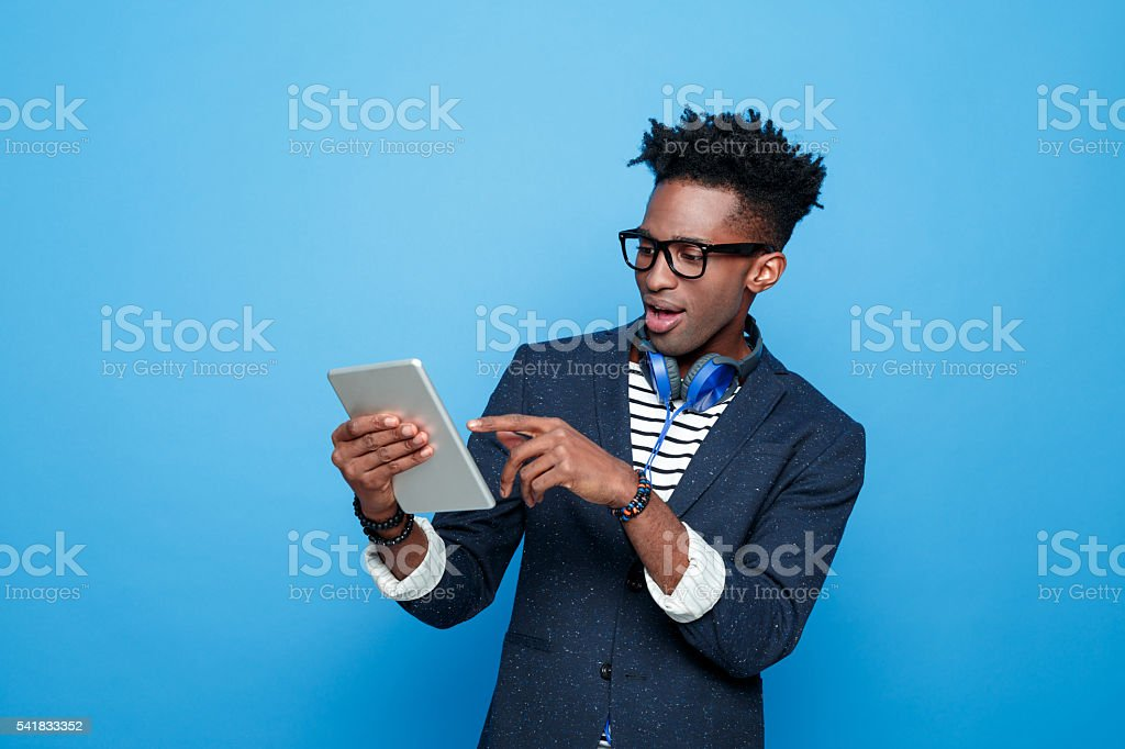 Excited afro american guy in fashionable outfit, holding digital tablet stock photo