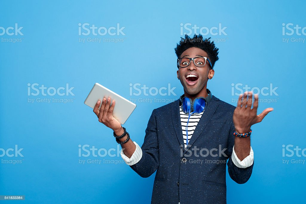 Excited afro american guy in fashionable outfit, holding digital tablet Studio portrait of surprised afro american young man wearing striped top, navy blue jacket, nerd glasses and headphone, staring at camera with mouth open, holding a digital tablet in hand. Studio portrait, blue background. Adult Stock Photo