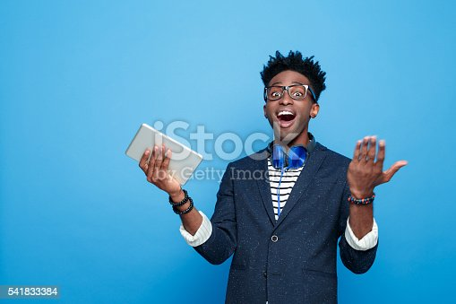 istock Excited afro american guy in fashionable outfit, holding digital tablet 541833384