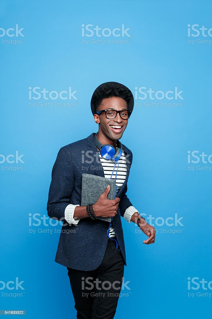 Excited afro american guy in fashionable outfit, holding notebook Studio portrait of happy afro american young man wearing striped top, navy blue jacket, hat, nerd glasses and headphone, smiling at camera, holding a notebook in hand. Studio portrait, blue background. Adult Stock Photo