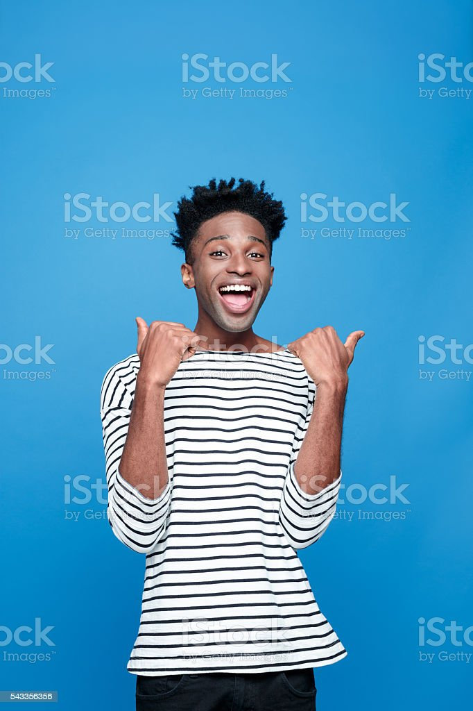 Excited afro american guy Portrait of happy afro american young man wearing striped top, laughing at camera with thumbs up. Studio portrait, blue background. Adult Stock Photo