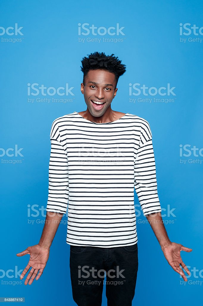 Excited afro american guy Portrait of happy afro american young man wearing striped top, laughing at camera. Studio portrait, blue background. Adult Stock Photo