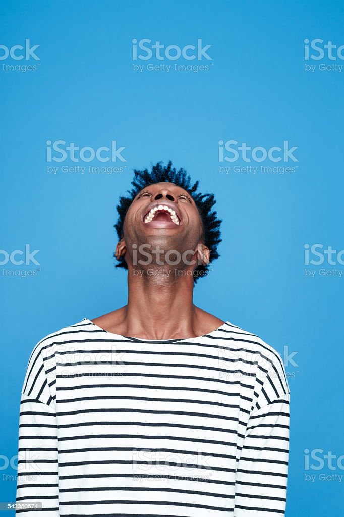 Excited afro american guy Portrait of happy afro american young man wearing striped top. Studio portrait, blue background. Adult Stock Photo