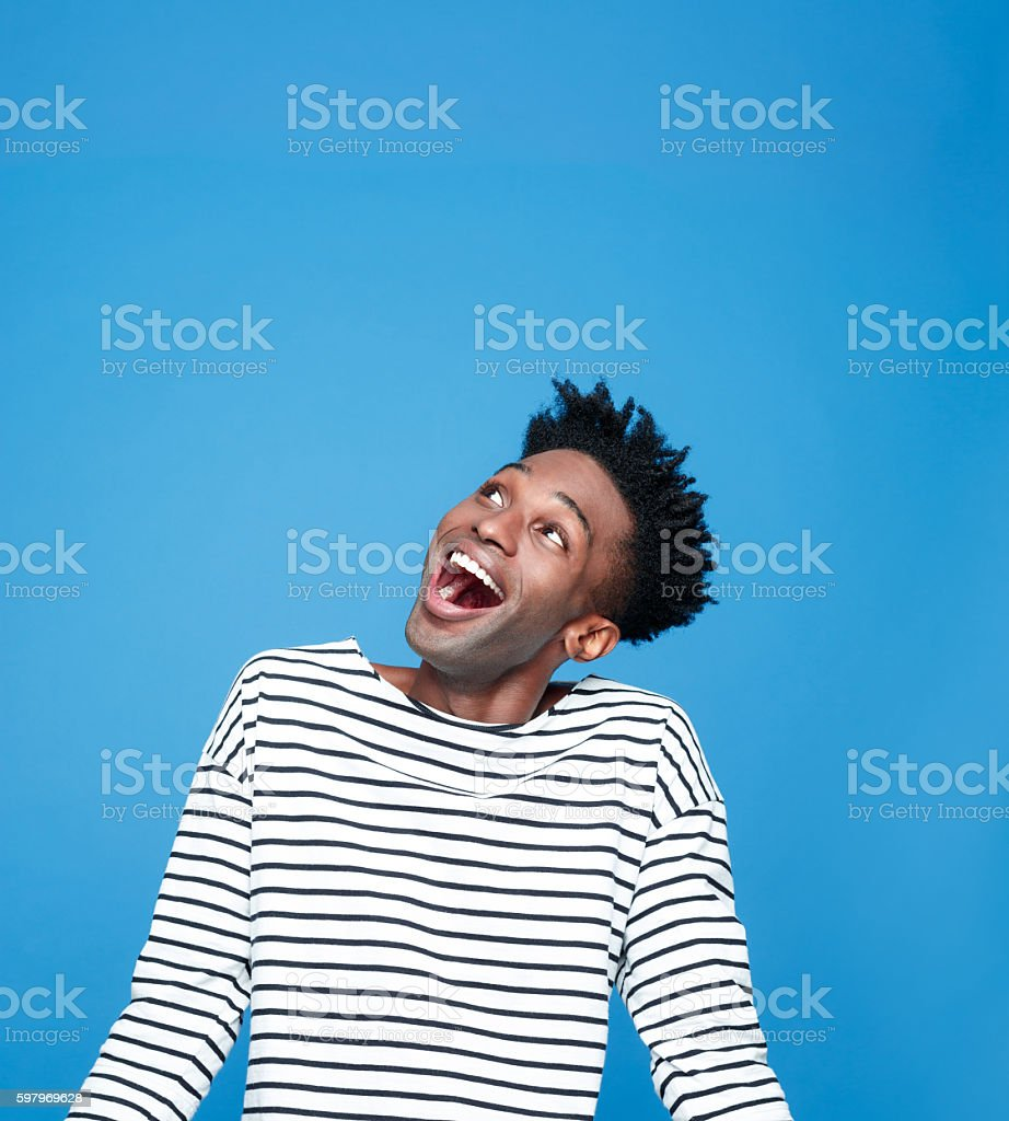 Excited afro american guy Portrait of happy afro american young man wearing striped top, looking up and laughing. Studio portrait, blue background. Adult Stock Photo