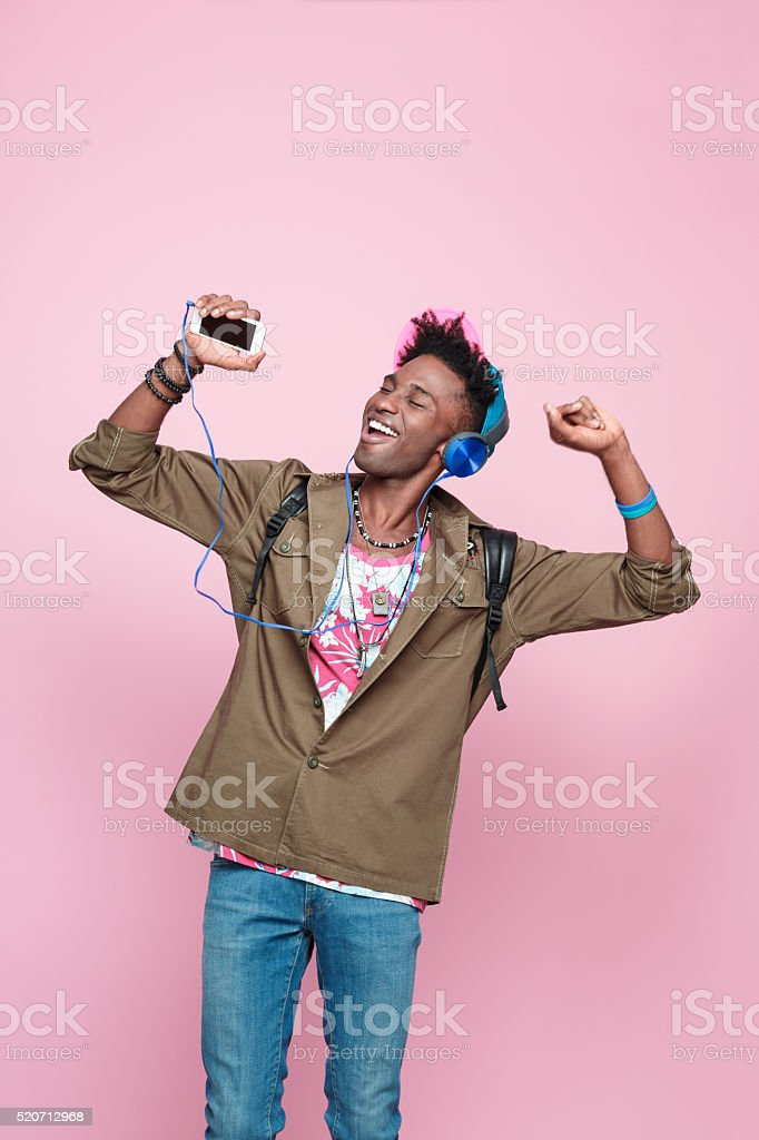 Excited afro american guy wearing headphone, dancing stock photo