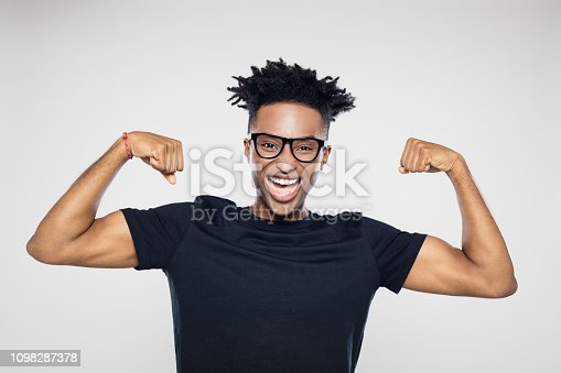 Portrait of excited young afro american man flexing his muscles against gray background