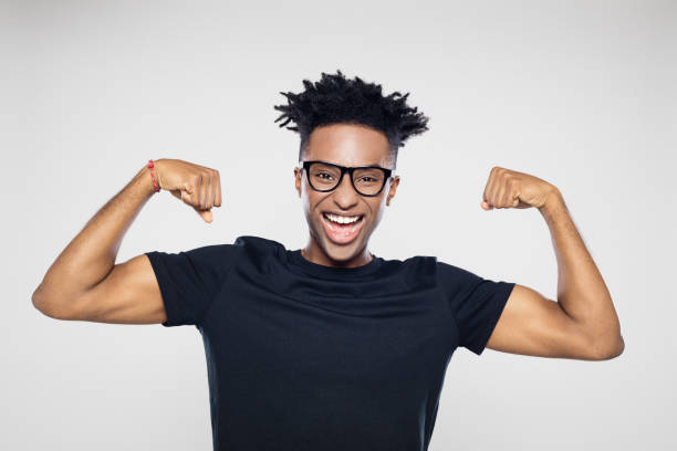 Excited afro american man flexing muscles Portrait of excited young afro american man flexing his muscles against gray background flexing muscles stock pictures, royalty-free photos & images